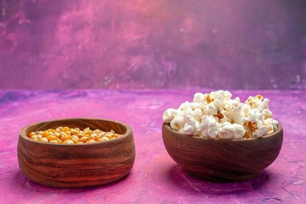 Vista frontal de pipoca fresca com grãos crus na mesa cor de rosa milho filme cinema cor