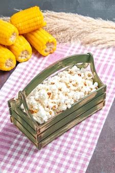 Vista frontal de pipoca fresca dentro de caixa de madeira no chão escuro, salgadinho de pipoca de milho
