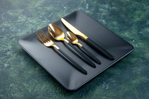Vista frontal de placas pretas com garfo e faca de colheres douradas em fundo escuro