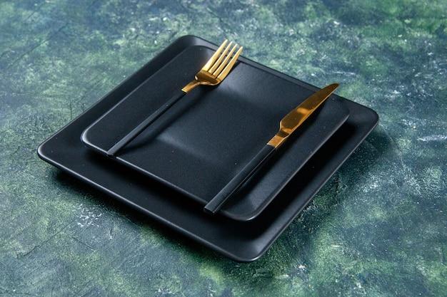 Vista frontal de placas pretas com garfo e faca dourados em fundo escuro