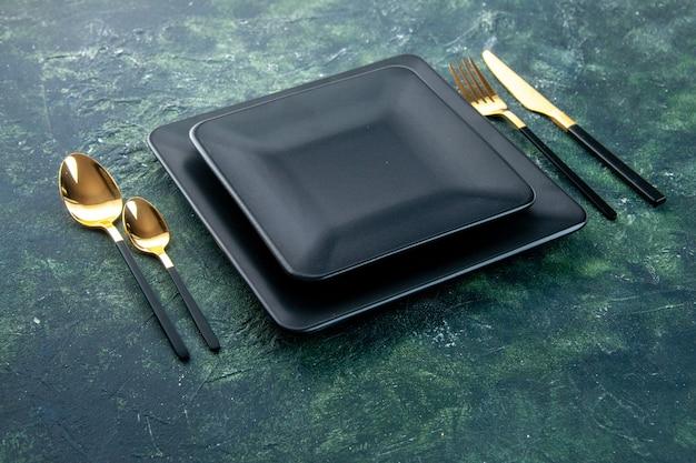 Vista frontal de placas quadradas pretas com colheres de garfo douradas e faca em fundo escuro