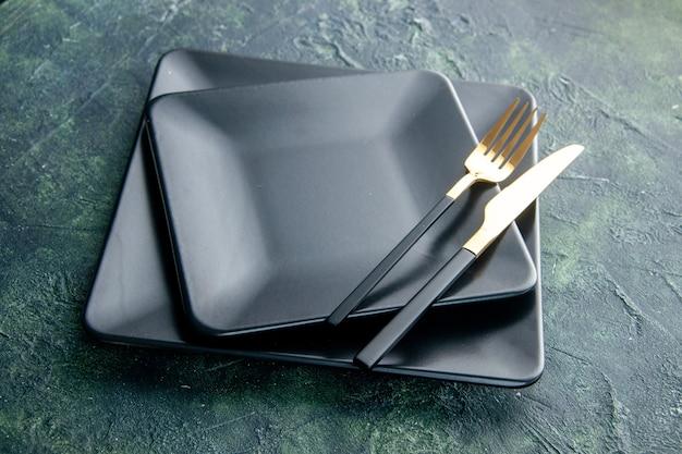 Vista frontal de placas quadradas pretas com garfo e faca dourados em fundo azul escuro