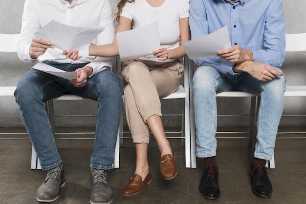Vista frontal de possíveis funcionários aguardando entrevistas de emprego