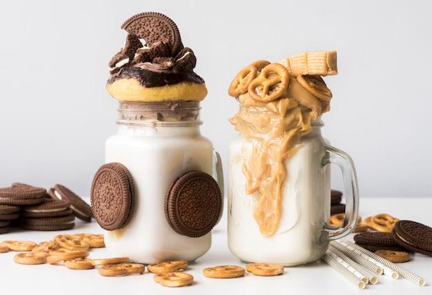 Vista frontal de potes de sobremesa com biscoitos e pretzels