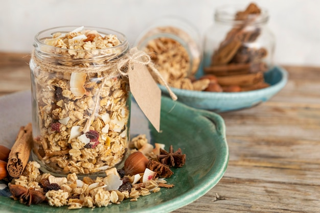 Vista frontal de potes transparentes no prato com cereais matinais e etiqueta