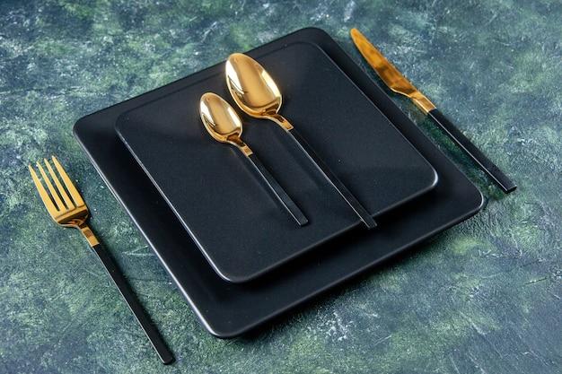 Vista frontal de pratos escuros com colheres douradas, garfo e faca em fundo azul escuro