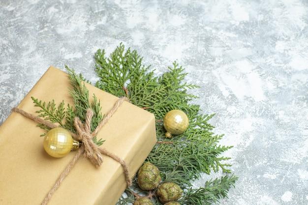 Vista frontal de presentes de natal com galho verde sobre fundo branco