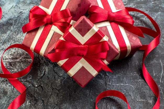 Vista frontal de presentes em caixas lindamente embaladas e amarradas com fita de cetim para a pessoa amada na mesa escura