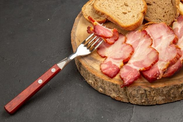 Vista frontal de presunto fresco fatiado com fatias de pão na cor escura do lanche.