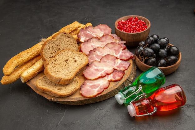 Vista frontal de presunto fresco fatiado com pãezinhos de frutas e fatias de pão na cor escura da refeição.