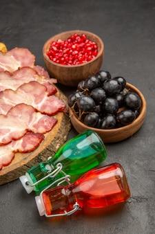 Vista frontal de presunto fresco fatiado com pãezinhos de frutas e fatias de pão na mesa escura.