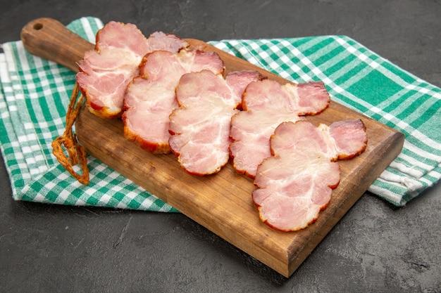 Vista frontal de presunto fresco fatiado em mesa de madeira e cor de porco cru