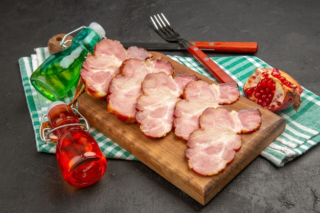 Vista frontal de presunto fresco fatiado em mesa de madeira e foto de comida cinza cor de porco cru