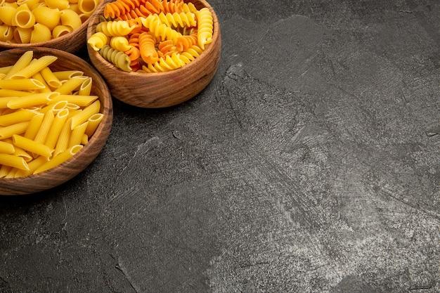 Vista frontal de produtos crus de composição de massa dentro de pratos em piso cinza.