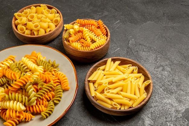 Vista frontal de produtos crus de diferentes composições de massas dentro de pratos no espaço cinza