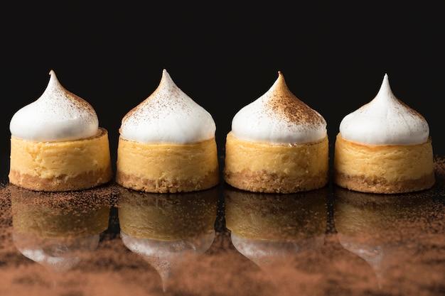 Vista frontal de quatro sobremesas com cacau em pó