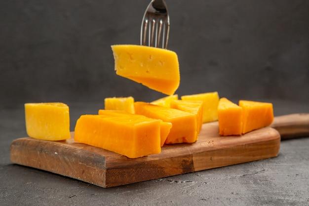 Vista frontal de queijo fresco fatiado com pãezinhos em uma refeição escura crocante de café da manhã