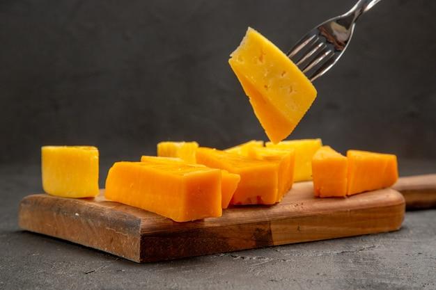 Vista frontal de queijo fresco fatiado com pãezinhos na cor escura de lanche crocante de café da manhã