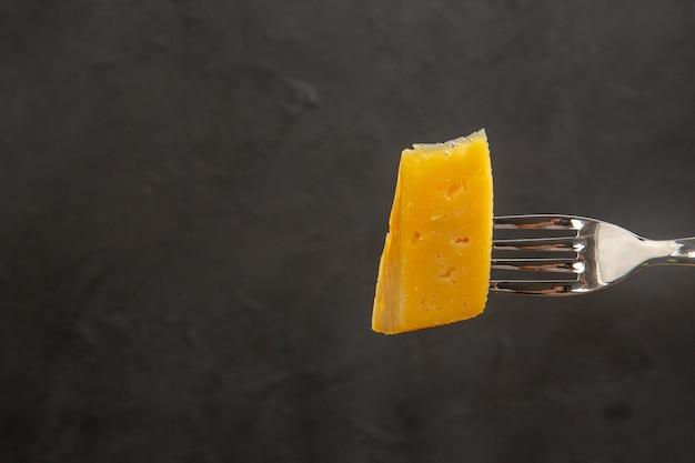 Vista frontal de queijo fresco fatiado no garfo foto colorida de lanche escuro café da manhã