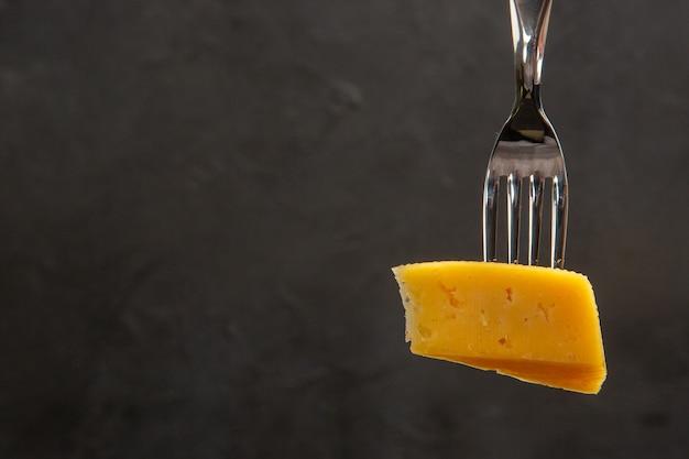 Vista frontal de queijo fresco fatiado no garfo refeição escura foto colorida café da manhã crocante