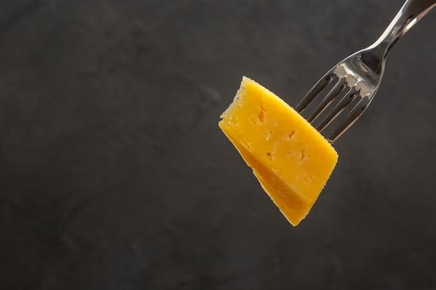 Vista frontal de queijo fresco fatiado no garfo refeição escura, foto colorida de café da manhã, batatas fritas