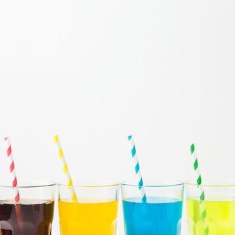 Vista frontal de refrigerantes em copos com canudos e espaço de cópia