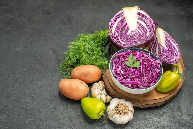 Vista frontal de repolho roxo fresco com legumes e verduras na mesa escura salada dieta saudável saúde