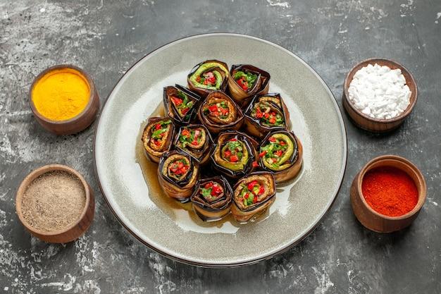 Vista frontal de rolos de berinjela recheada pimenta em pó açafrão sal marinho pimenta preta em pequenas tigelas na foto do prato cinza