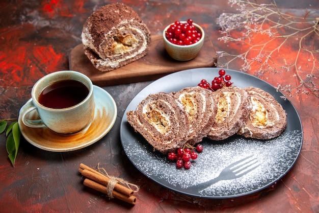 Vista frontal de rolos de biscoito com xícara de chá na superfície escura