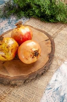 Vista frontal de romãs em uma tábua de corte de madeira redonda galho de árvore de pinho