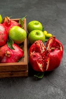 Vista frontal de romãs frescas com maçãs verdes na superfície escura de cor de frutas maduras