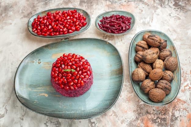 Vista frontal de romãs frescas com nozes em cor clara de frutas saúde foto porca
