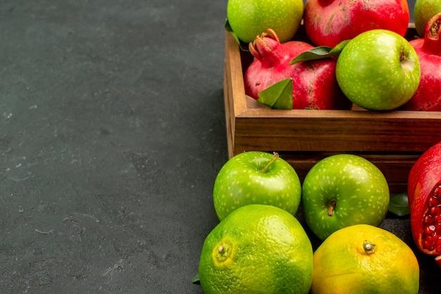 Vista frontal de romãs frescas com tangerinas e maçãs em frutas maduras de superfície escura