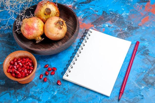 Vista frontal de romãs frescas em uma tigela de madeira uma tigela com sementes de romã um caderno caneta vermelha sobre fundo azul