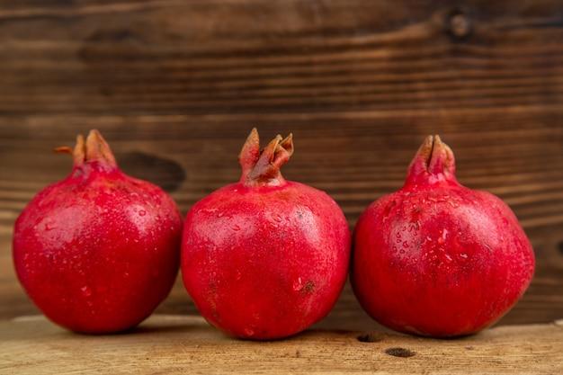 Vista frontal de romãs frescas na mesa de madeira, cor, suco de frutas, foto, árvore, vermelho