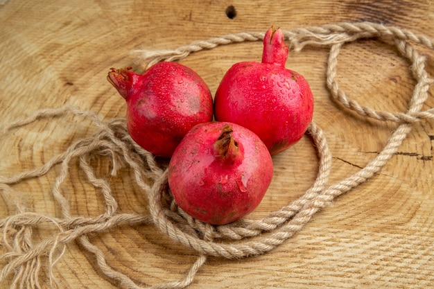 Vista frontal de romãs vermelhas com cordas em uma mesa de madeira colorida árvore de suco
