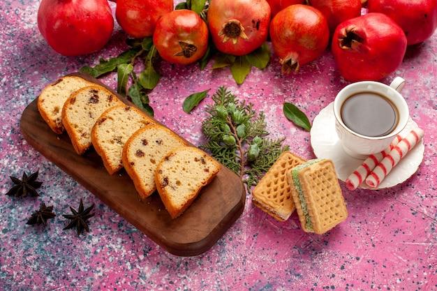 Vista frontal de romãs vermelhas frescas com bolo fatiado, chá e waffles na mesa rosa