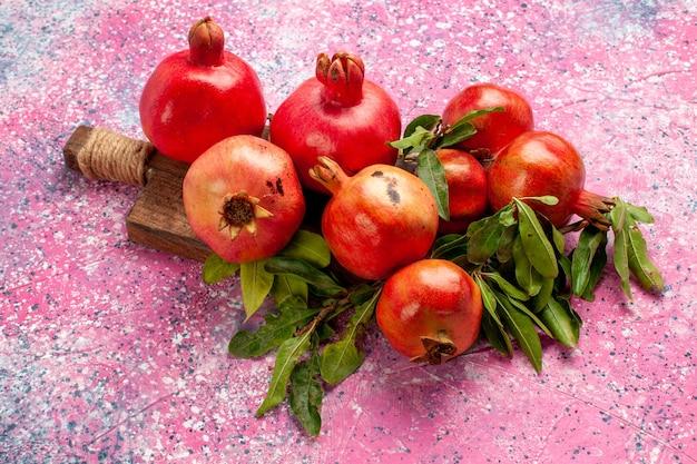 Vista frontal de romãs vermelhas frescas com folhas verdes na superfície rosa