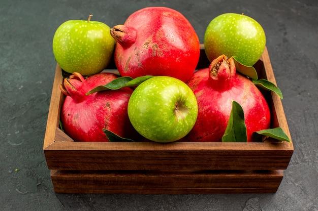 Vista frontal de romãs vermelhas frescas com maçãs verdes na superfície escura de cor de frutas maduras