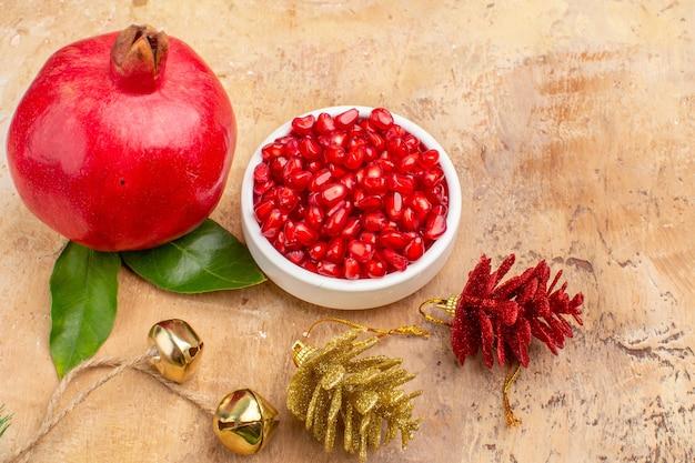 Vista frontal de romãs vermelhas frescas descascadas e com frutas inteiras em um fundo marrom foto colorida de frutas suco suave