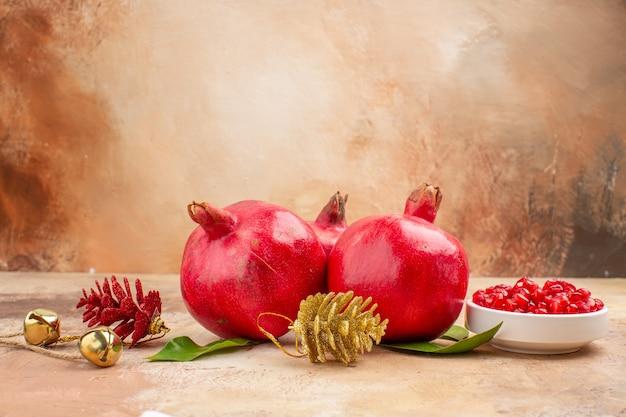 Vista frontal de romãs vermelhas frescas em fundo claro cor de frutas foto suco suave