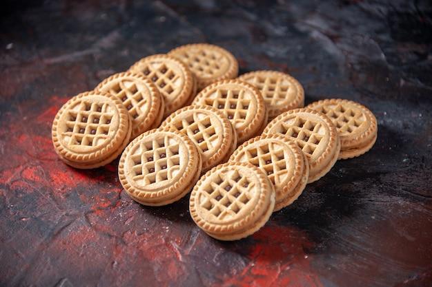 Vista frontal de saborosos biscoitos de açúcar colocados lado a lado em três fileiras em um fundo de cores com espaço livre