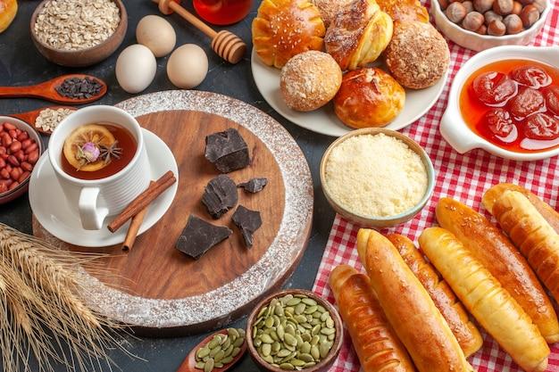 Vista frontal de saborosos pastéis doces com chá de geléia e pãezinhos na parede escura