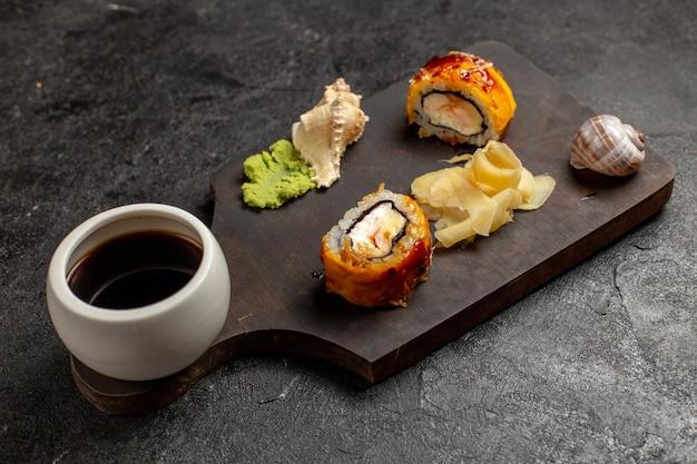 Vista frontal de saborosos rolos de peixe de refeição de sushi com molho wassabi na parede cinza