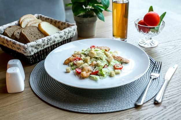 Vista frontal de salada caesar com frango em um prato com fatias de pão branco e preto e com um refrigerante em cima da mesa