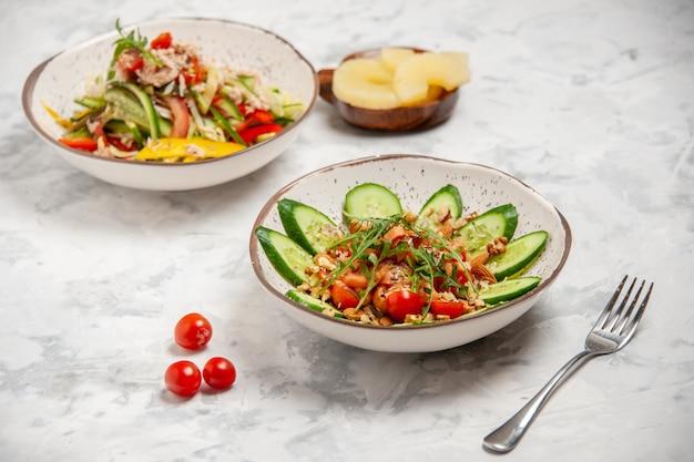 Vista frontal de saladas veganas saudáveis em tigelas com garfo e tomate seco com abacaxi em uma superfície branca manchada com espaço livre