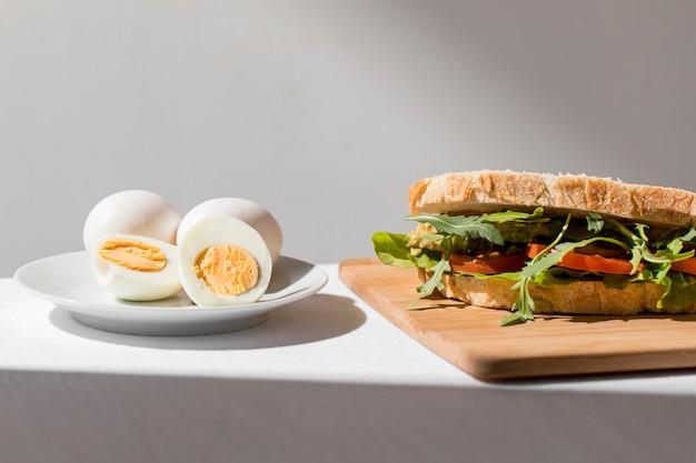 Vista frontal de sanduíche de torrada com tomate e ovos cozidos