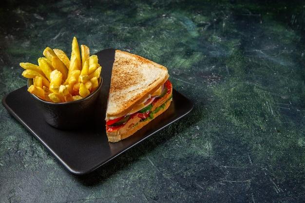 Vista frontal de sanduíches de presunto com batatas fritas dentro do prato em superfície escura