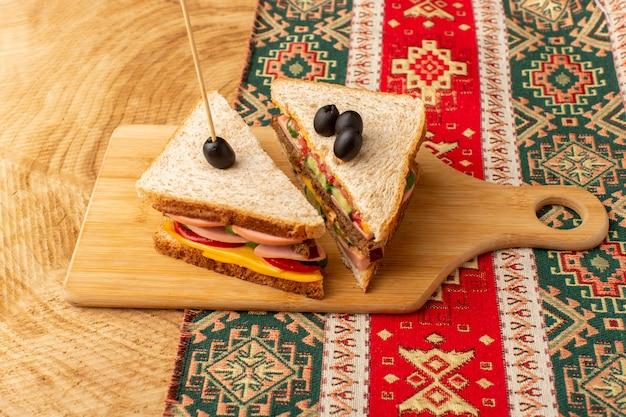 Vista frontal de sanduíches saborosos com presunto e tomate verde-oliva na madeira