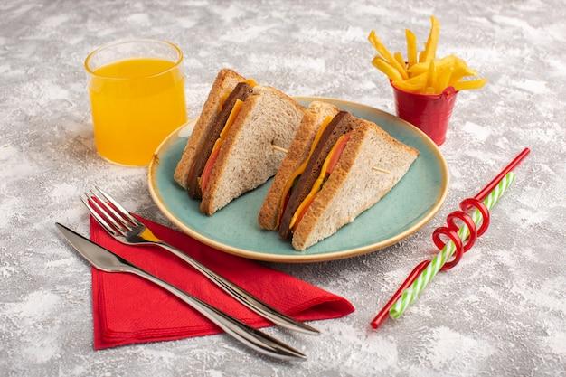 Vista frontal de sanduíches saborosos de torradas com presunto de queijo dentro de prato azul com suco de batatas fritas